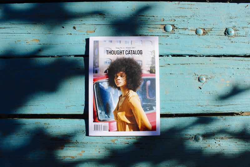 Reading a magazine at a rustic table under a tree photo by Thought Catalog (2017)